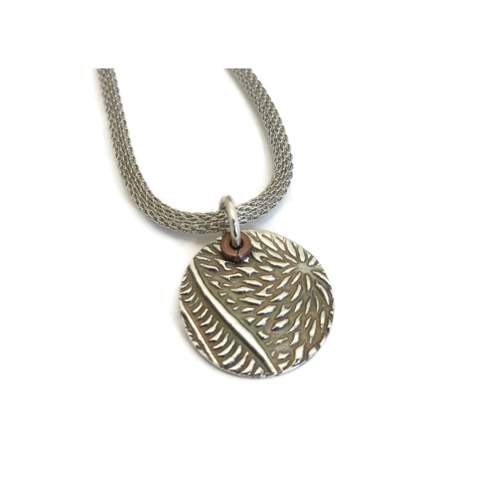 Textured and darkened fine silver circle pendant made from silver metal clay suspended on a silver woven necklace.