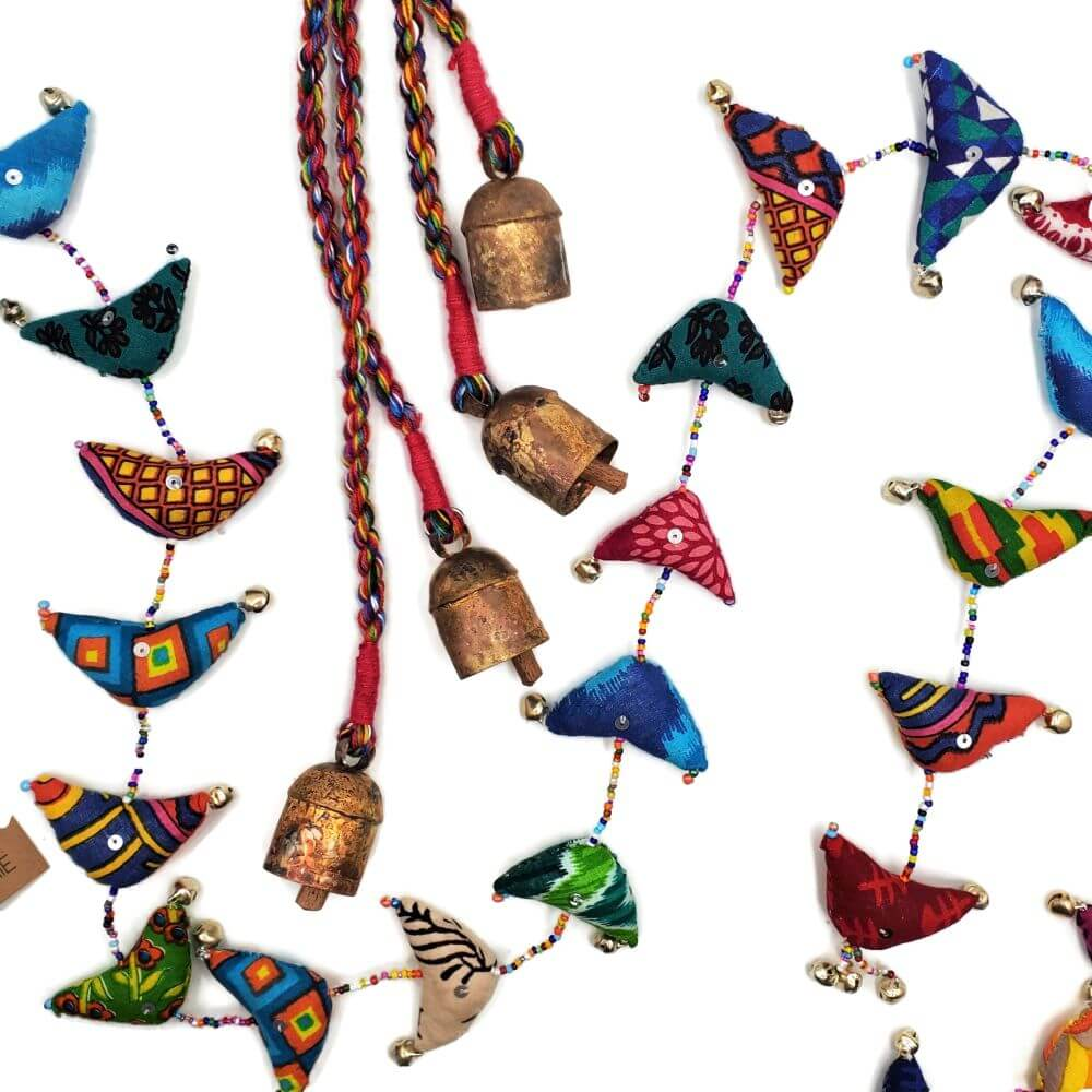 Song Bird Garland made of recycled sari fabric, seed beads, and small bells.  A second product featuring 4 large bells on brightly colored braided cord is also pictured..
