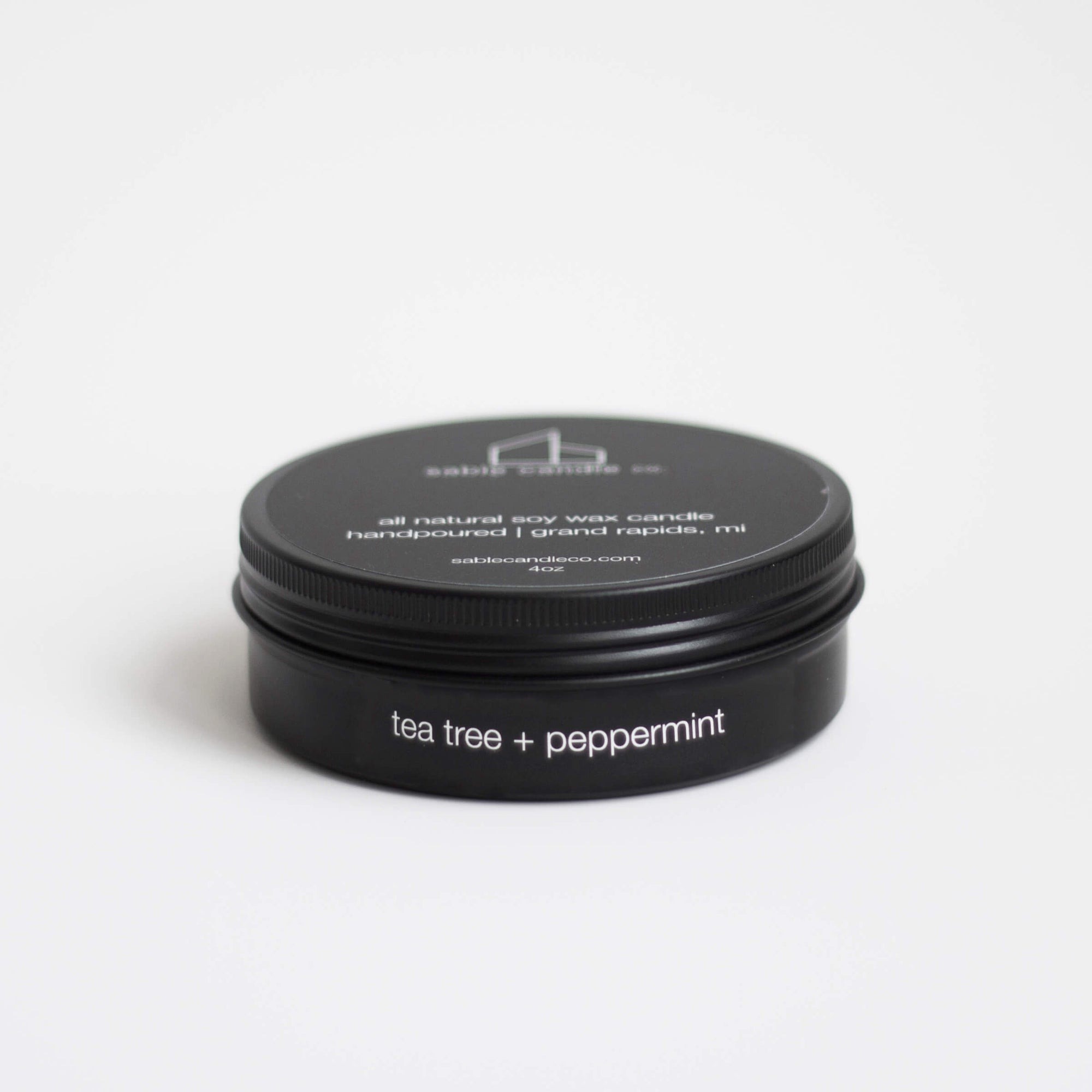 "A small black metal container with a screw top black lid. White words read ""tea tree + peppermint""."