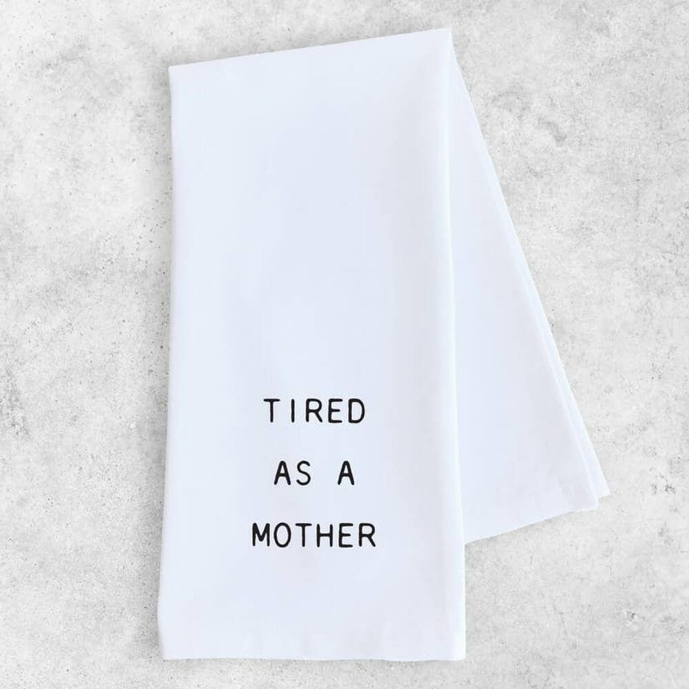 "Folded white kitchen towel with black capital letters reading ""Tired as a Mother""."