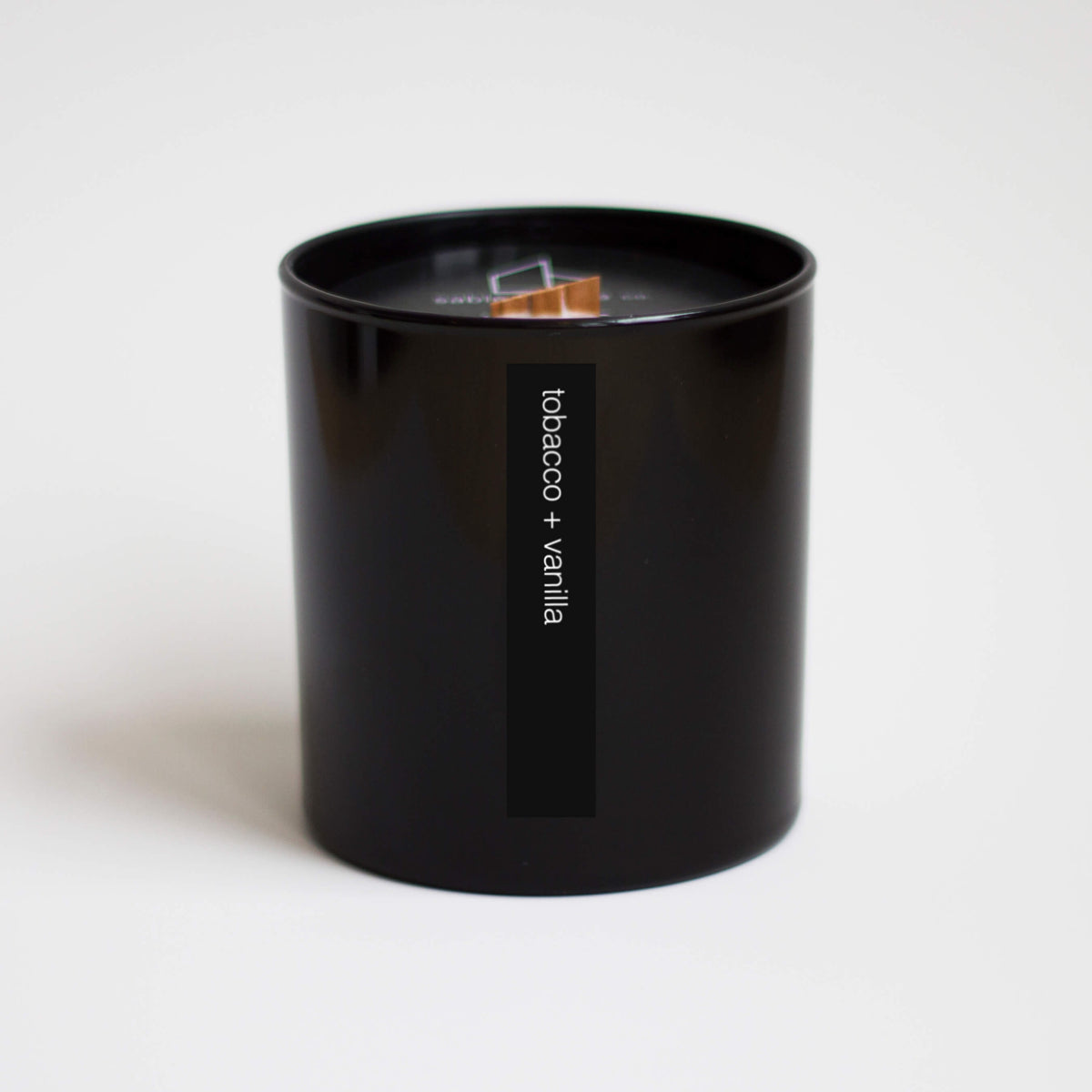 "Tall black container holding beige candle with wood wick. Words on outside read ""tobacco + vanilla""."