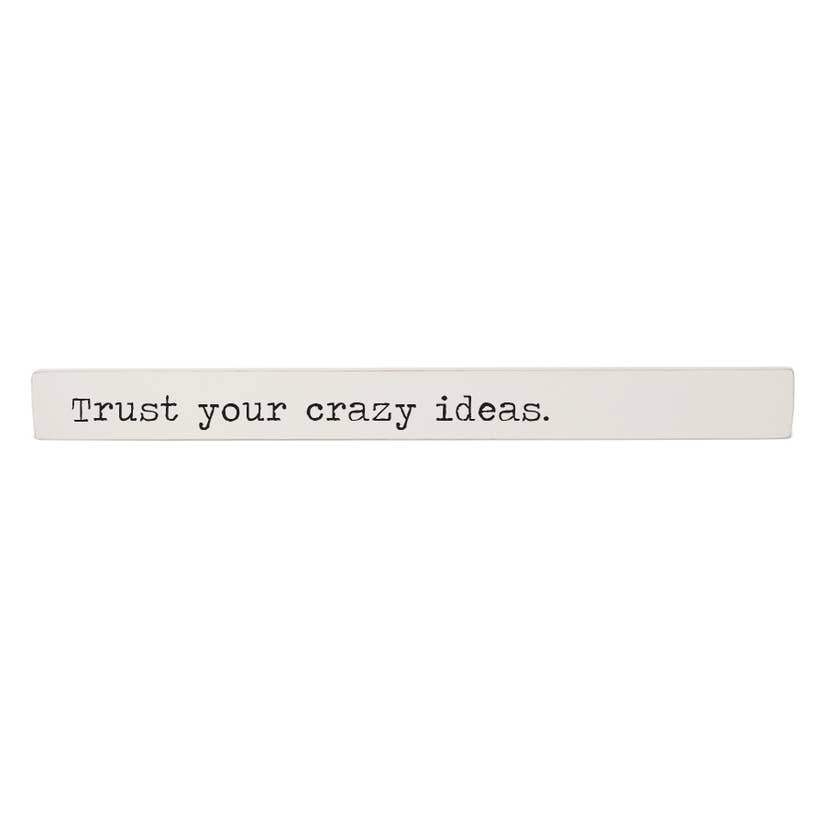 "Painted wooden stick with a black typewriter style font reading ""Trust your crazy ideas""."