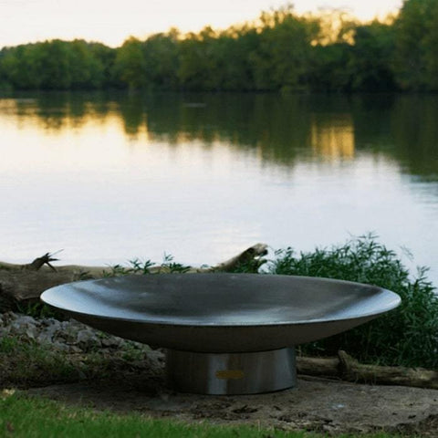 "Bella Vita 34"" Stainless Steel Fire Pit by Fire Pit Art with Tress and Pond Background"