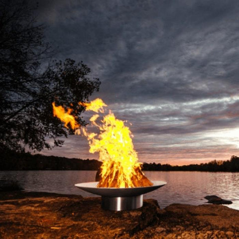 "Bella Vita 34"" Stainless Steel Fire Pit by Fire Pit Art With Trees and Sunset Background"