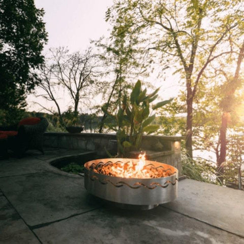 Fire Surfer Stainless Steel Fire Pit by Fire Pit Art with Tress Background