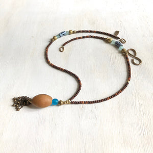 Hand painted blue Adinkra African beads with vintage olive wood pendant long necklace. Cristina Tamames Jewelry Designer