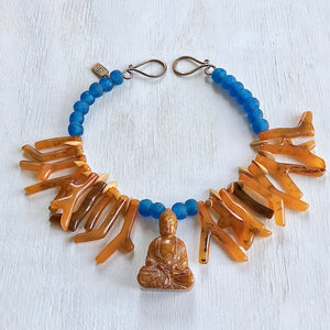 Orange shapes of resin coral necklace with blue recycled glass African beads and a Buddha as the center piece. Cristina Tamames Jewelry Designer