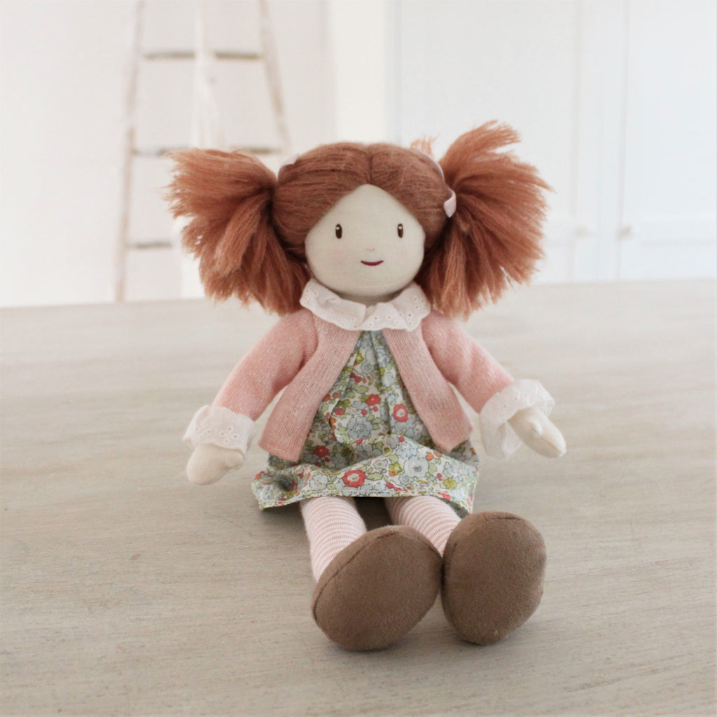 plastic-free rag soft doll with bunches and floral dress with pink cardigan