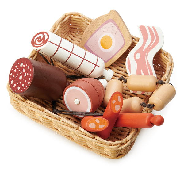 A hand crafted wicker basket with continental charcuterie set that is part of the market stall range. This set includes a slice of ham and egg pie, a black sausage, a rasher of bacon, a string of butchers sausages, a large salami, a spanish corizo style sausage, and a ham hock.