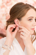 Beautiful bride putting on her pearl and cz earrings