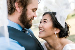 Bride showing off her long crystal bride earrings to groom