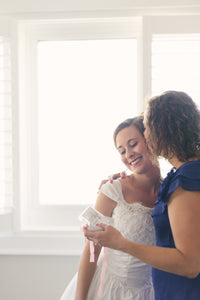 Mother of the bride hugging daughter on wedding day