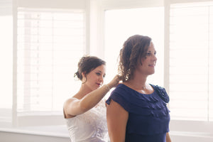 Bride putting necklace on mother of the bride on wedding day