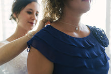 Bride placing necklace on mother of the brides neck