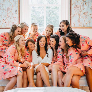 Gorgeous bride surrounded by her bridesmaids after giving them bridesmaid gifts