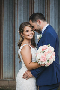 bride and groom embrace during wedding pictures rose gold wedding earrings