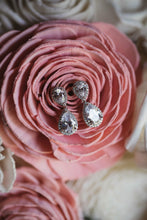 Silver teardrop earrings displayed on brides bouquet on wedding day