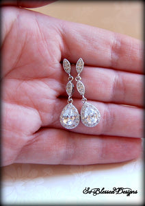 Bride holding long crystal earrings on wedding day
