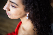 bride putting on marquise teardrop earrings on wedding day