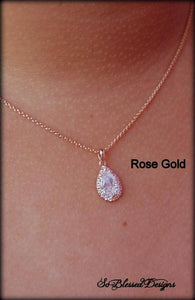 rose gold teardrop pendant worn by mother of groom