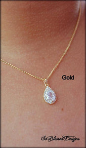Gold teardrop pendant worn by mother of the bride