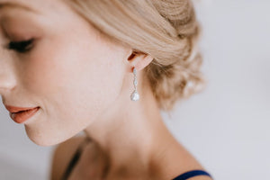 bridesmaid wearing long delicate silver and crystal earrings