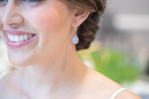 Bride smiling looking at her wedding earrings