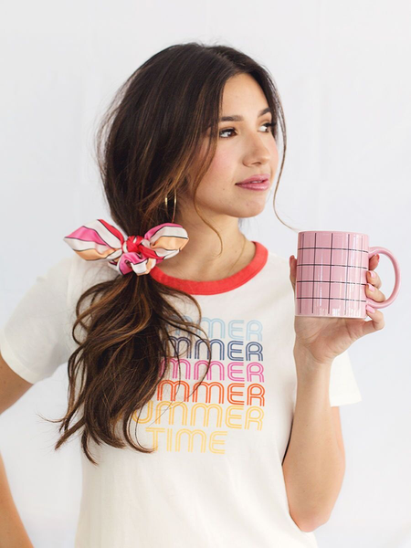Brunette woman with a scarf in her hair holding a pink grid coffee mug.