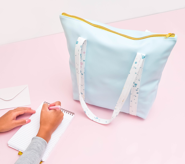 a cute tote bag in light blue vegan leather with white paint splatter straps and zippered top next to a taskpad