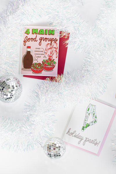 "Two holiday greeting cards. The one at the top left is white with a pink square containing the text ""4 Main food groups"" in green and red. There is a bottle of syrump, a jar of candy canes, a bowl of red, white and green candy corn and another bowl of wrapped red, white and green candies. There is text ""Candy"", ""Candycane"", Candycorn"" and ""Syrup"" with arrows pointing to each item. The card on the lower right is white with a pair of pink and green holiday graphic decorated pants and the text ""Holiday Pants"""