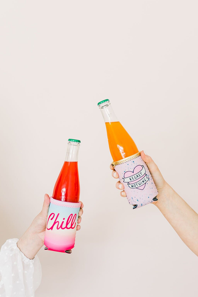 "Two hands holding beverage insulators holding bottles. The one on the left is rainbow gradient with pink bias and the word ""Chill. The one on the right is pink with a multi colored splatter print with a heart and banner with the words ""Regret Nothing"""