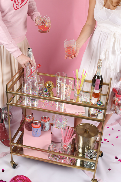 Two women standing over a gold beverage cart with various glass cups and bottles of champagne.