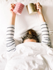 Girl hiding under the covers holding her arms up with a pink and gold coffee mug in her hands.
