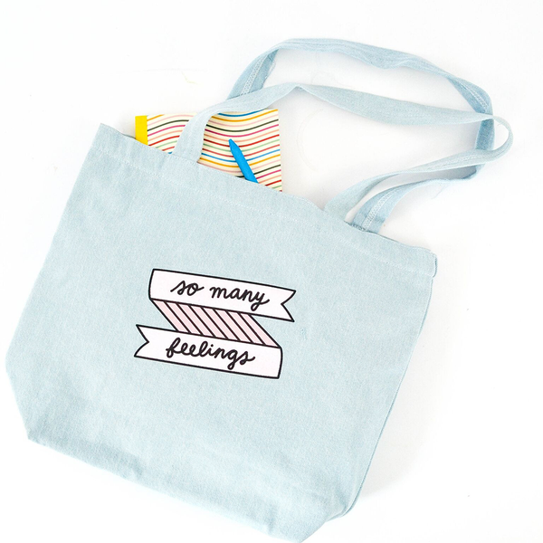 A beachwash denim tote with pink so many feelings banner print with a small notebook laying halfway inside of it with a blue pen.