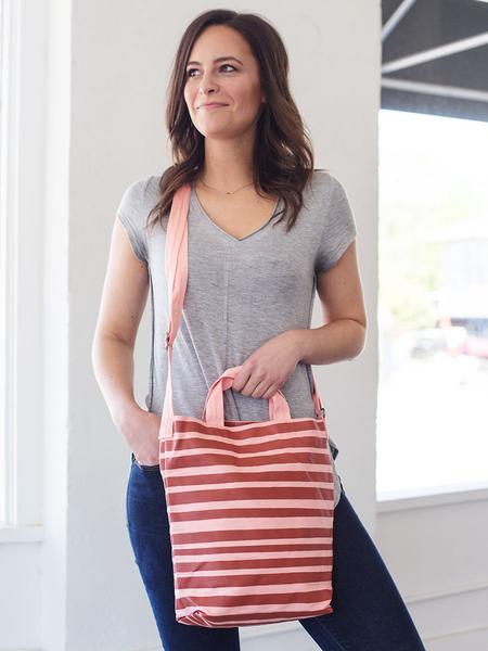 Brunette girl wearing a cute crossbody tote in peach canvas with red stripes.