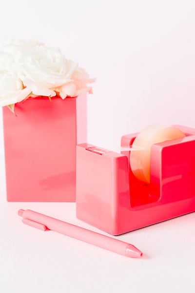 Lifestyle photo of neon coral tape dispenser, pen, and pen cup with flowers in it.