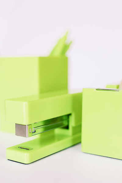 Lifetsyle photo of a citron green stapler with a matching tape dispenser and pen cup in the background.