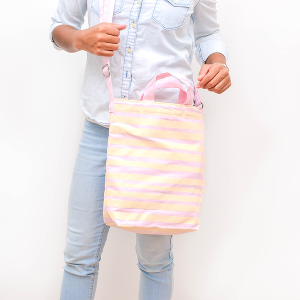 A woman stands in a washed denim shirt with a pink and yellow striped crossbody tote to her side.