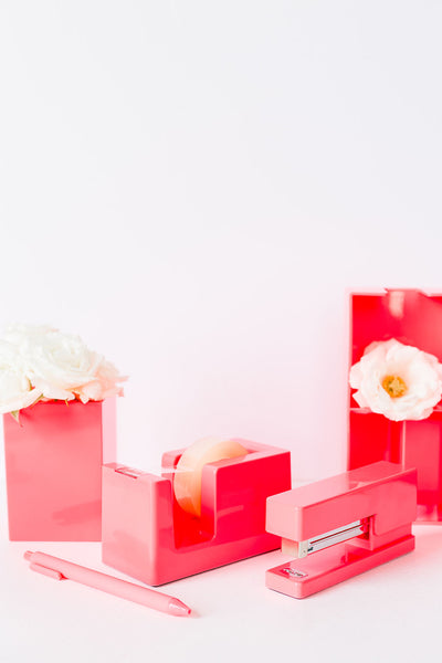 Lifestyle photo of neon coral tape dispenser, tray,  pen, and pen cup with flowers in it.