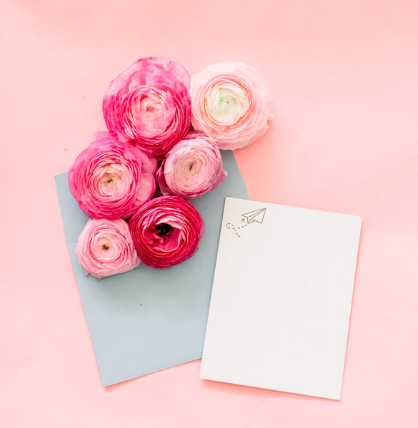 A cute letter pressed card featuring a paper airplane surrounded by pink flowers.