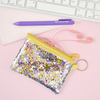 Glitter confetti coin pouch is sitting on a desk with pink earbuds and a purple pen.