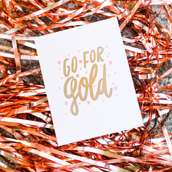 "White greeting card with gold text ""Go For Gold"" and pink stars. The card is laying on metallic ribbon."