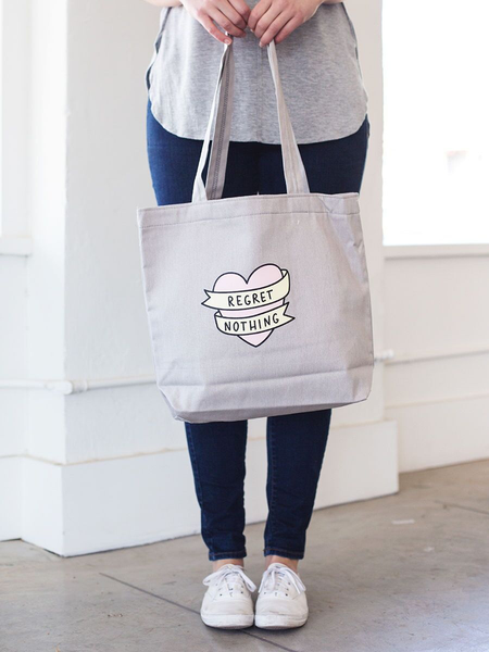 Girl in white sneakers holding a cute tote bag in gray canvas with regret nothing banner heart design..