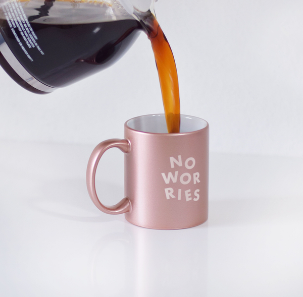 Coffee being poured into No Worries Rose Gold Mug is a funny coffee mug with pink lettering.