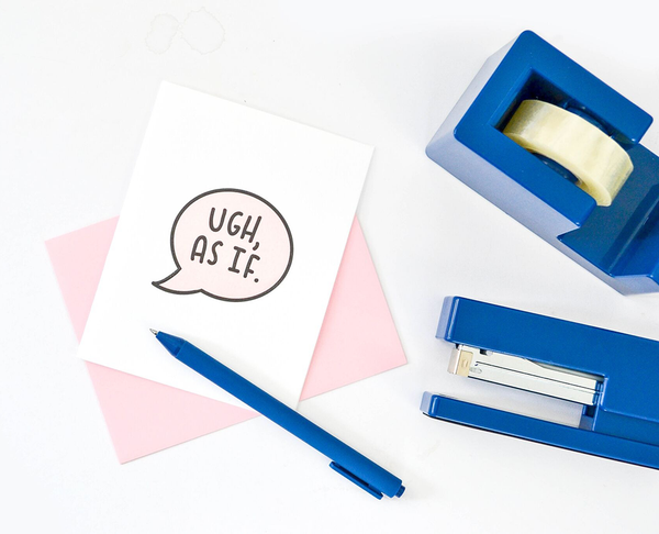 "White greeting card with a text bubble in black and light pink with ""Ugh, As If."" There is a pink envelope, a blue jotter pen, blue tape dispenser and blue stapler next to it."