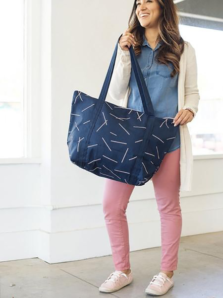 Brunette girl holding a cute tote bag in navy blue canvas with long shoulder strap and zippered top.
