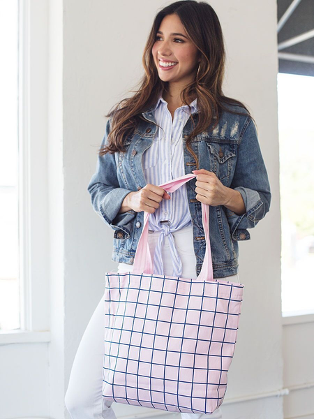 Smiling brunette girl in a denim jacket holding a cute tote bag in blush pink with grid pattern.