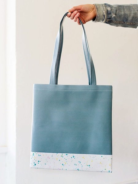 Girl's hand holding a spruce green tote bag with white paint splatter detail along the bottom.