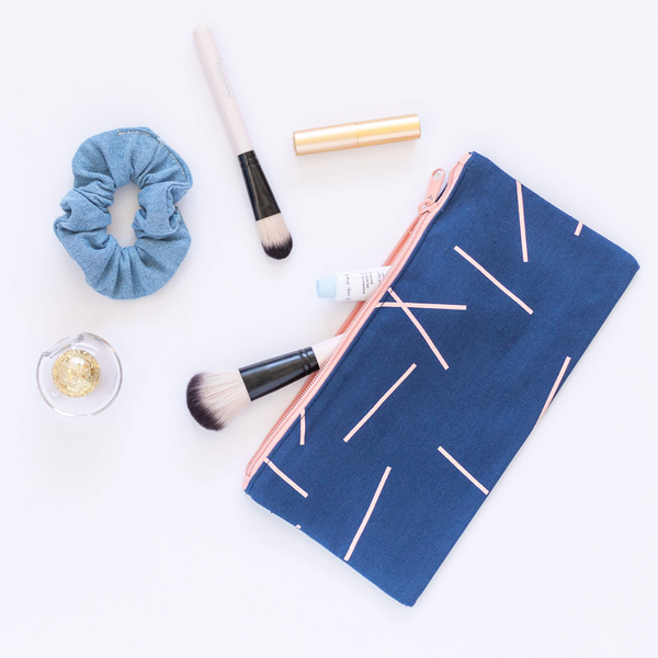 Large pencil pouch in navy blue canvas with peach pixie sticks pattern. makeup brushes and beauty products in the bag.