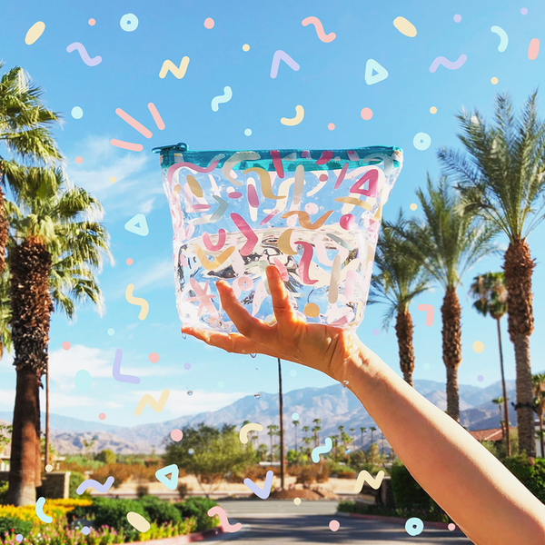 Woman stands holding clear vinyl bag with colorful wiggles drawn on it, with a blue sky and palm trees in the background